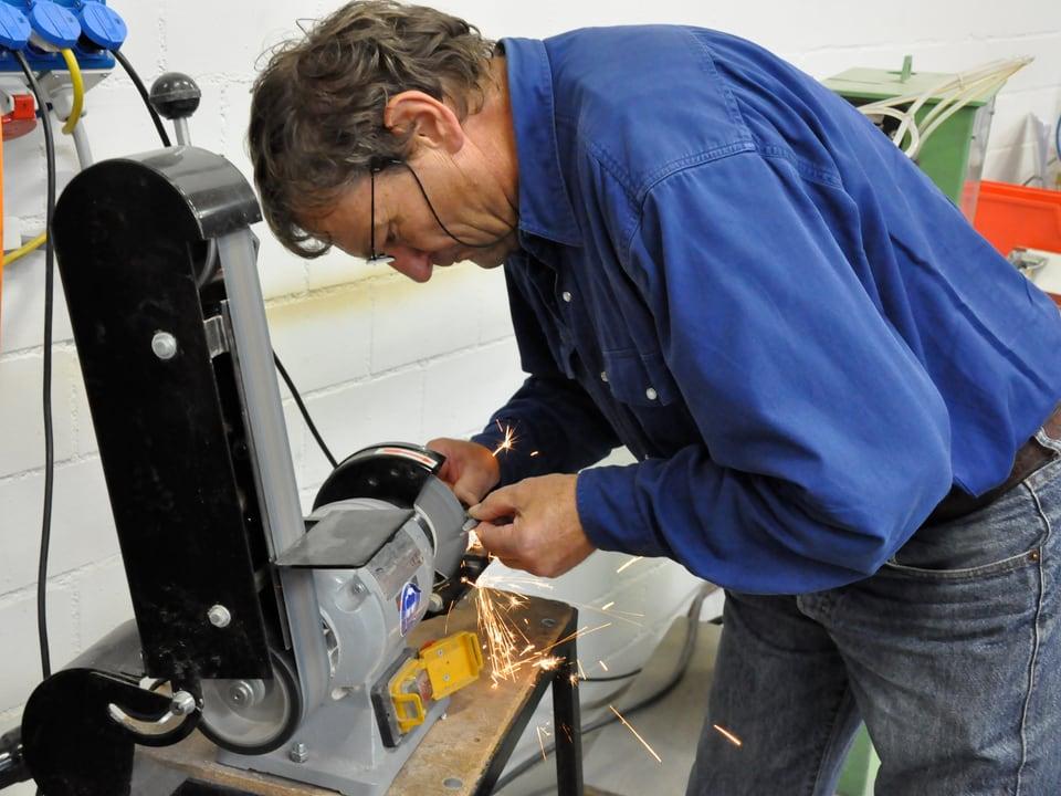 Ein Mann arbeitet an einer Schleifmaschine