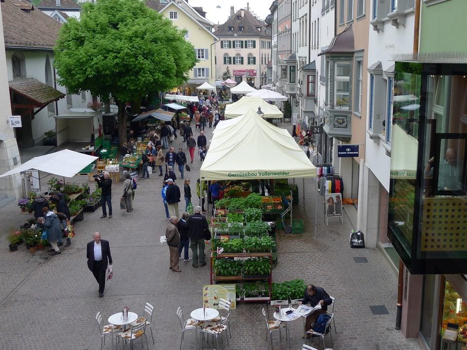 Ein Blick von leicht erhöhter Lage über die Vordergasse in der Altstadt von Schaffhausen. Linkerhand ist ein stattlicher Baum zu sehen. Rechterhand der Erker einer Konditorei, unten drei Bistrotische. In der Vordergasse die überdachten Marktstände mit flanierenden Leuten.