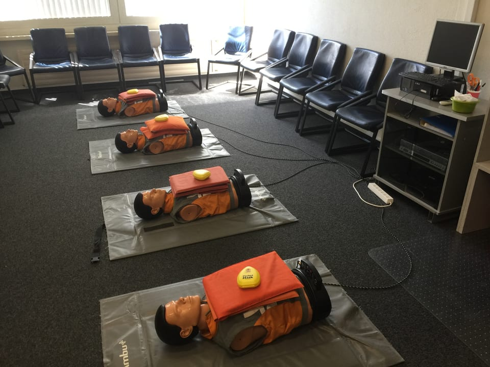 Puppen liegen am Boden. An ihnen üben die Flight-Attendants den medizinischen Notfall.