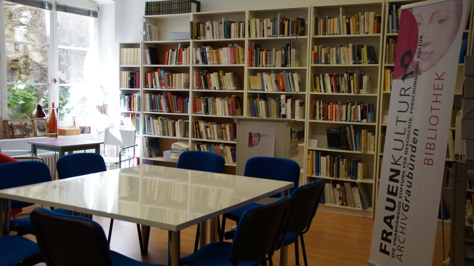 Sala cun ina maisa en mitad, sutgas blauas enturn ed enturn ed ina gronda curuna cun cudeschs vi da la paraid - quai è la biblioteca da l'archiv cultural da dunnas.
