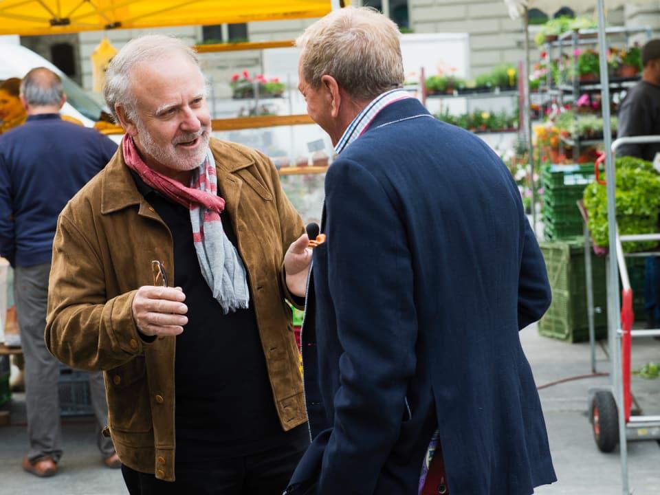 Peter Reber vertieft ins Gespräch mit Kurt Aeschbacher. Der Musiker trägt eine cognacfarbige Lederjacke, einen schwarzen Pullover und einen rotgrau gestreiften Schal.