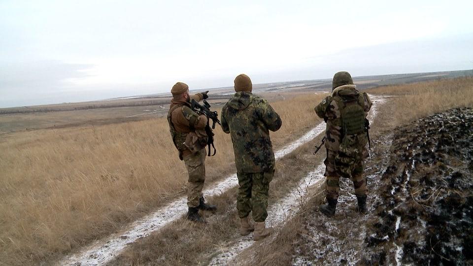 Drei bewaffnete Männer in Uniform auf Feldstrasse