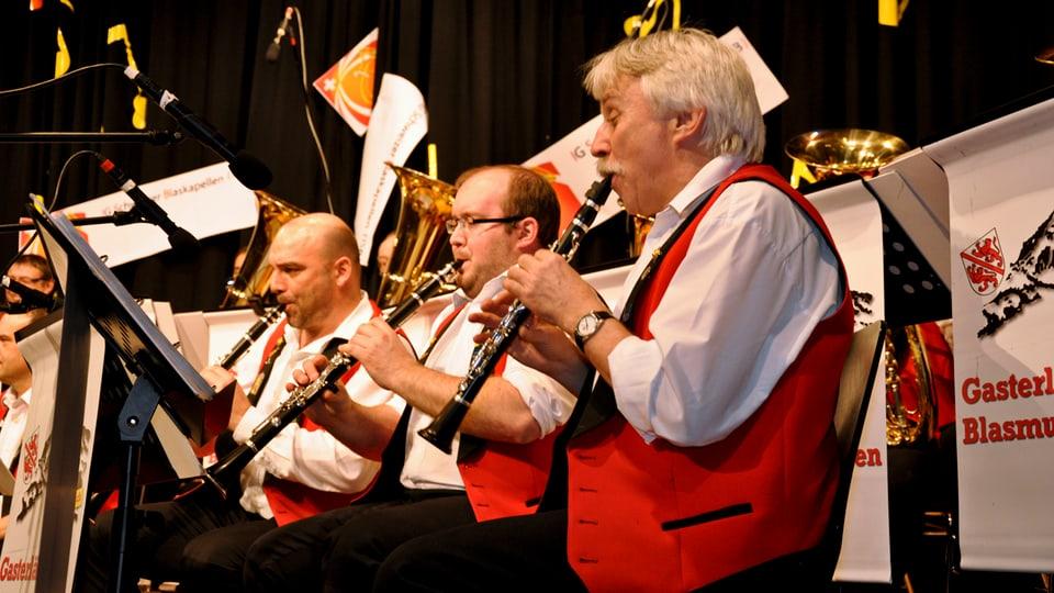 Drei Klarinettisten der Gasterländer Blasmusikanten in weissen Hemden und roten Gilets beim Auftritt in Wauwil.