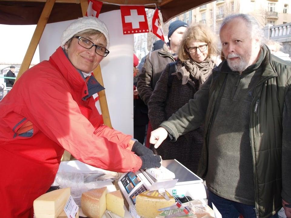 Barbara John mit Wollmütze und roter Windjacke bedient auf dem Wochenmarkt Kundschaft.