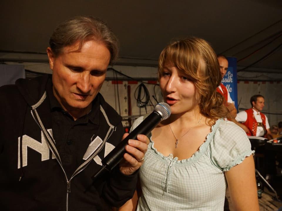 Moderator Beat Tschümperlin hält der jungen Frau das Mikrofon hin.