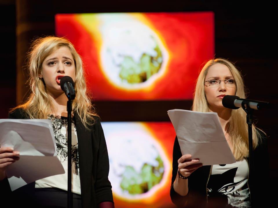 Lara und Martina stehen mit ernstem Blick an den Mikrofonen.