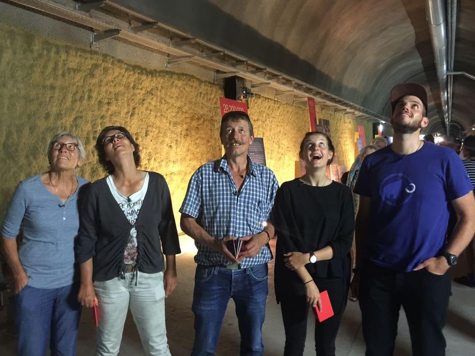 Fünf Personen schauen mit grossen Augen an die Decke in einem Tunnel
