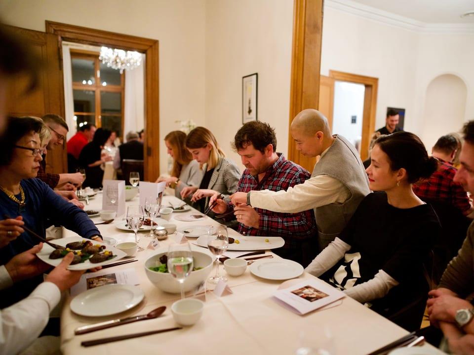 Die Köchin steht bei den Gästen am Tisch und erklärt.