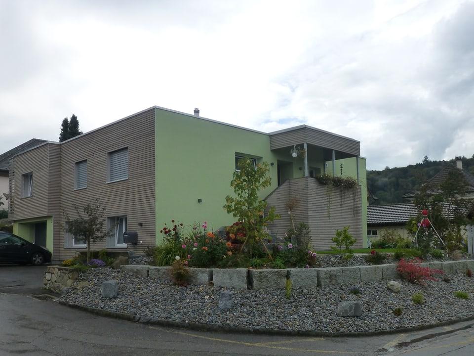 Modernes, grünes Wohnhaus mit punktueller Holzverkleidung.