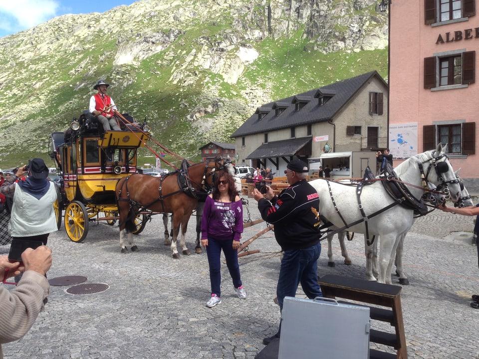 Touristen posieren auf der Gotthard-Passhöhe vor der alten Postkutsche.