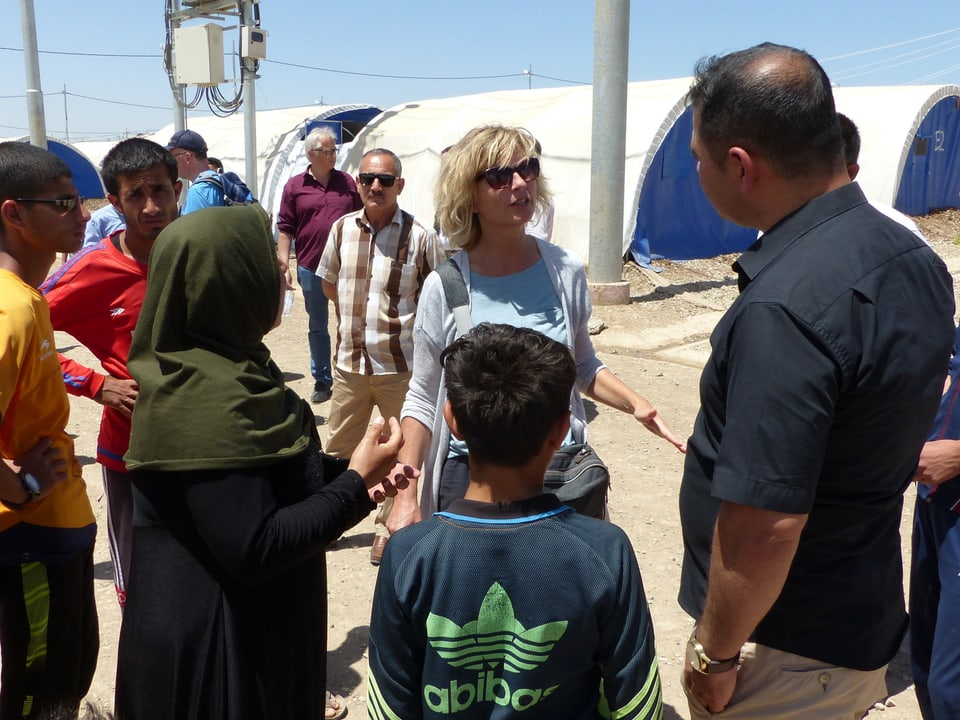 Reporterin Ladina Spiess diskutiert mit Leuten vom Flüchtlingslager.