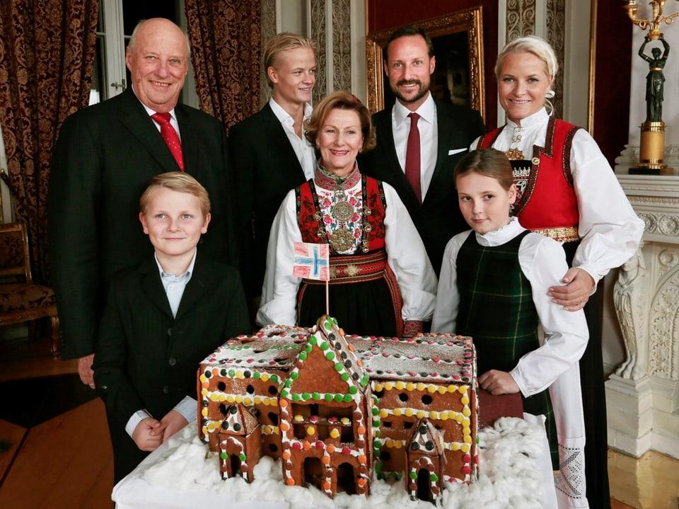 Die norwegischen Royals posieren um ein Lebkuchenhaus.
