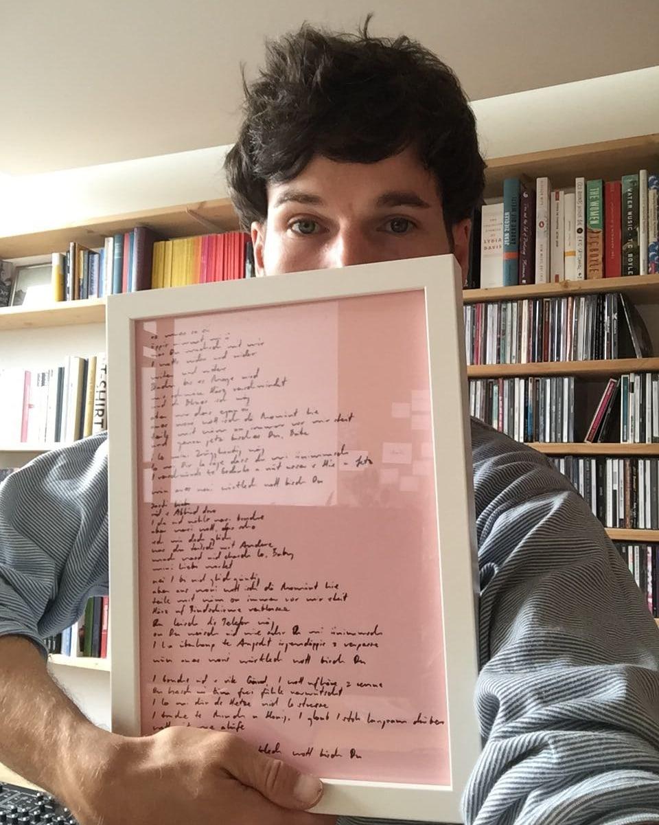 James Gruntz hält einen gerahmten Songtext in die Höhe.