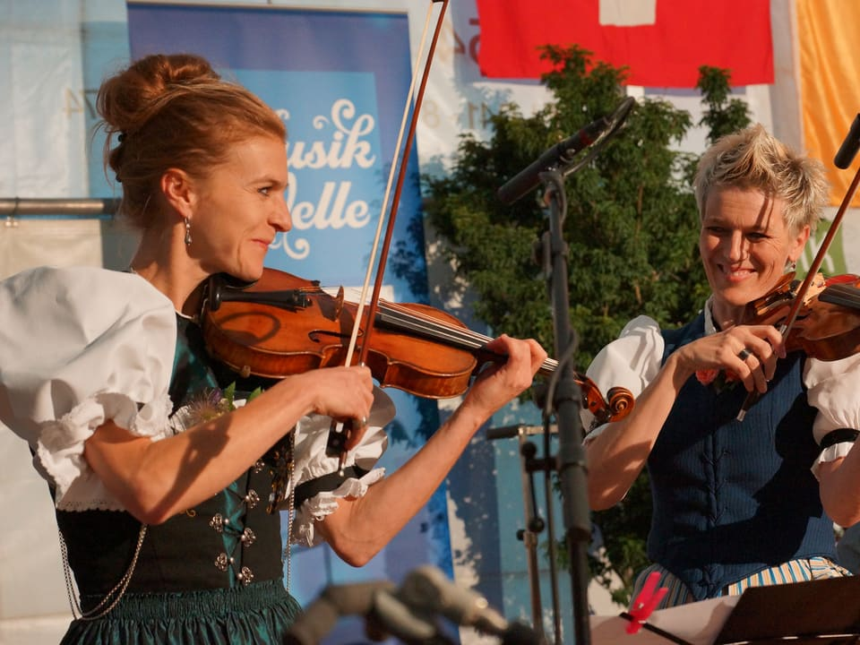 Die zwei Frauen in Trachten spielen Violine.