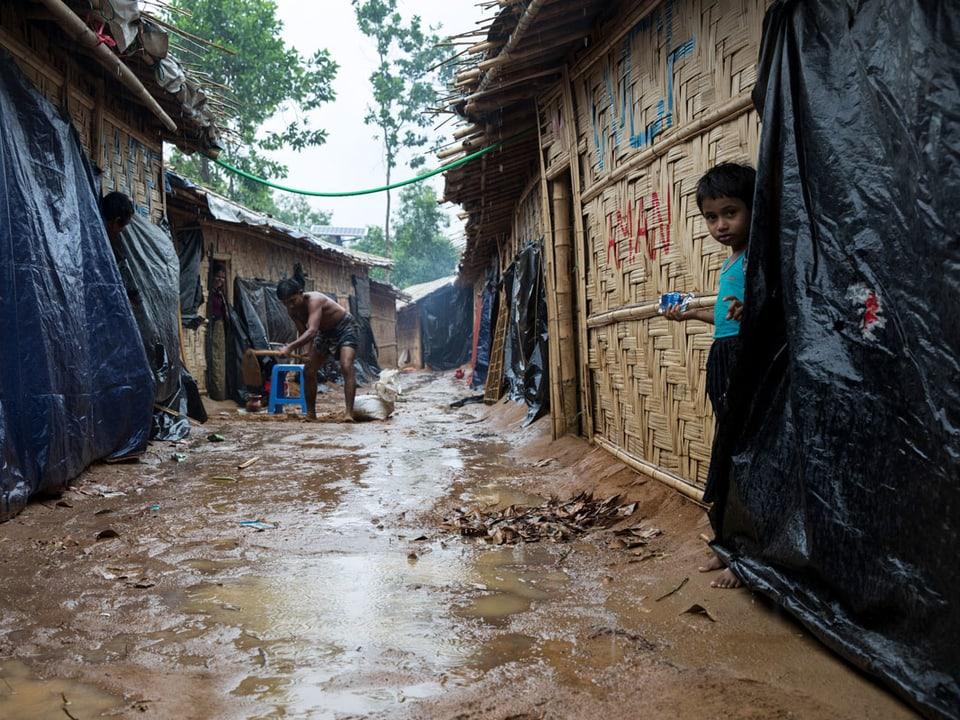Kinder stehen im Regen bei Hütten.