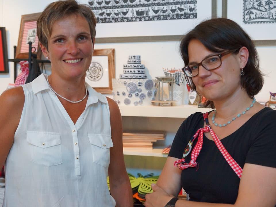Die zwei Frauen stehen im Laden vor einem Regal. An der Wand hängen grosse Scherenschnitte.