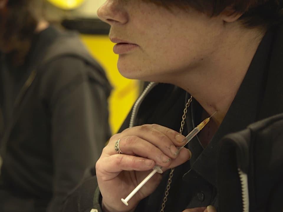 Eine Süchtige spritzt sich Kokain in den Hals.