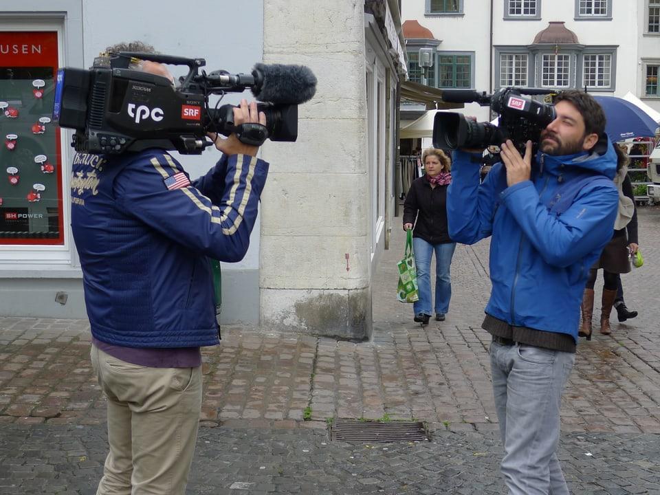 Die beiden Kameramänner stehen sich in naher Distanz gegenüber und zielen mit ihrer Kamera in die Richtung des anderen, um die Kameras einzustellen.