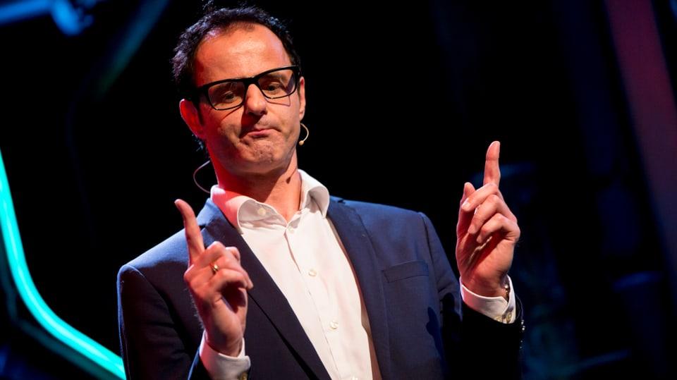 Vince Ebert auf der Bühne zeigt mit den Fingern die länge eines männlichen Penis.