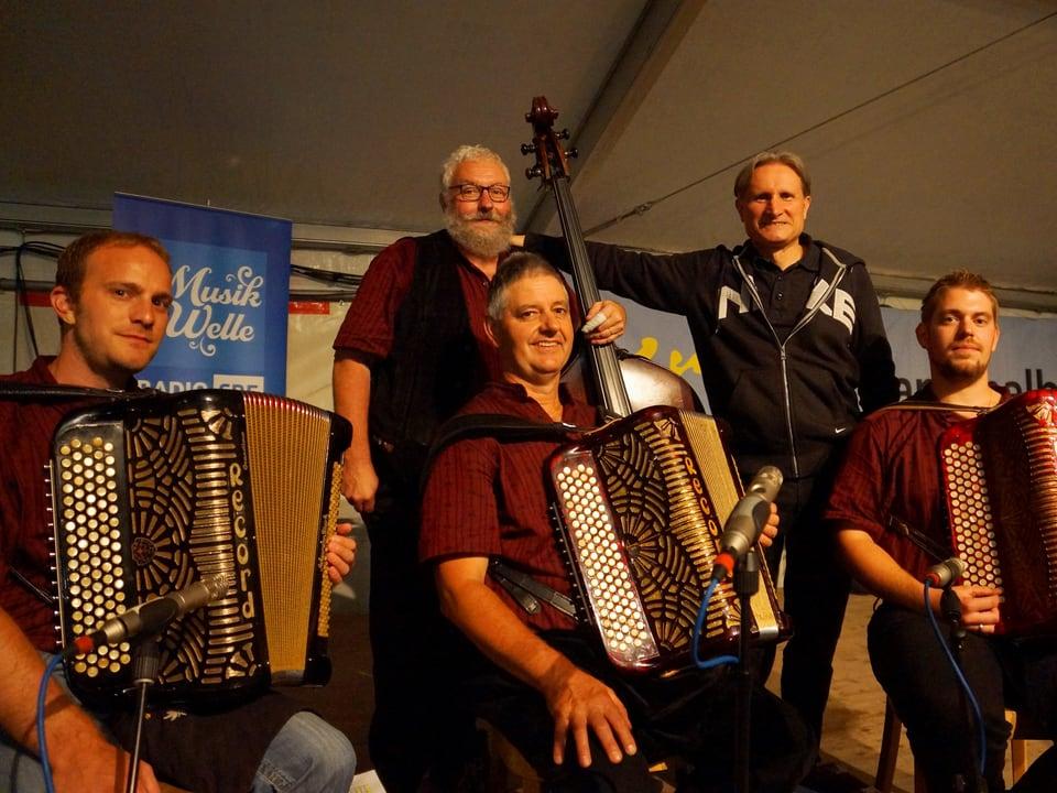 Drei Musikanten sitzend mit Akkordeon, ein Musikant stehend mit Kontrabass und ebenfalls stehend Beat Tschümperlin.