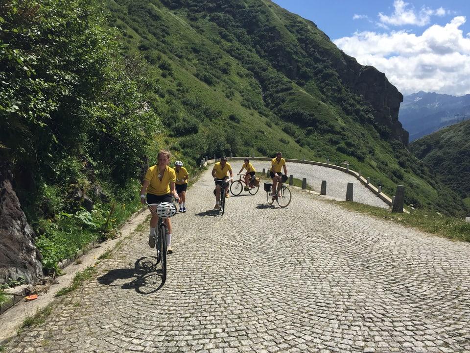 Blick auf die Tremola, fünf Menschen in gelben T-Shirts auf Velos