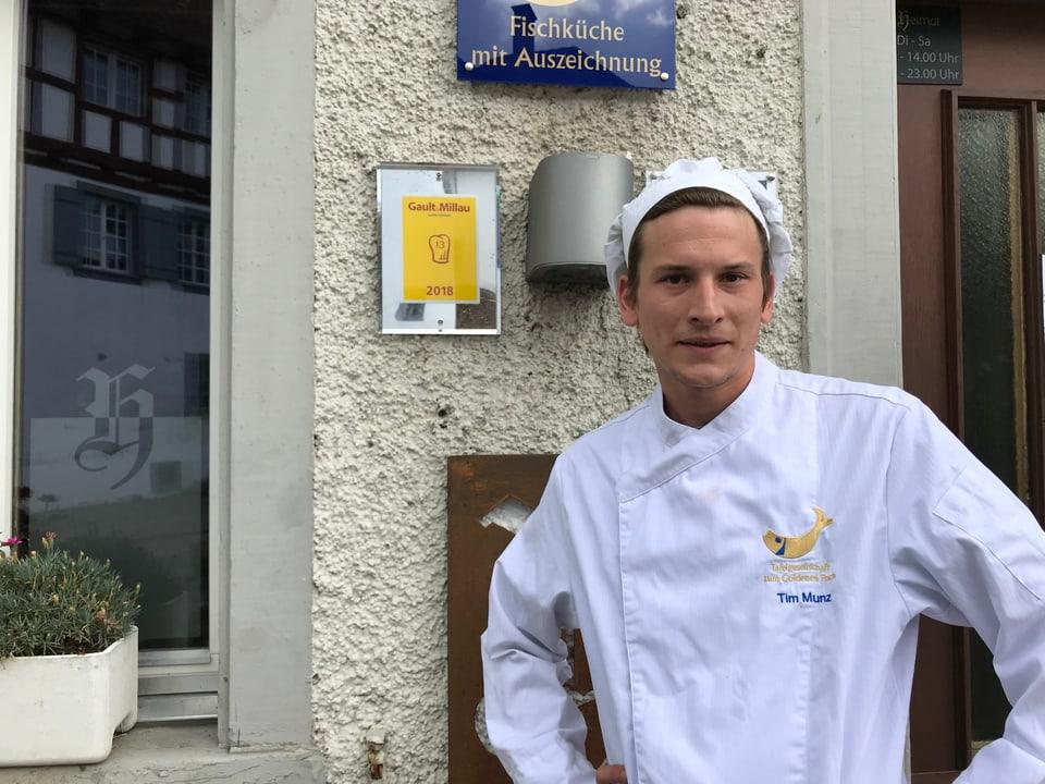 Koch steht vor einem Gault & Millau - Schild.