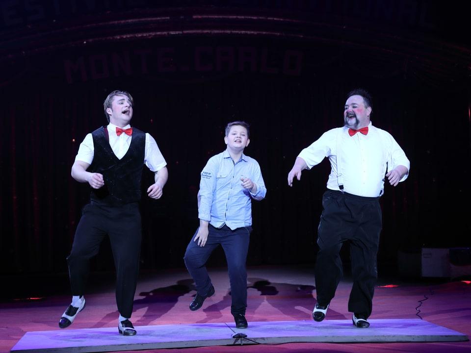 Drei Clowns tanzen in der Manege.
