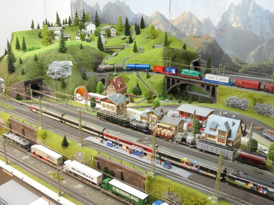 Modelleisenbahn, mehrere Geleise und Züge kreuzen eine idyllische Berglandschaft.