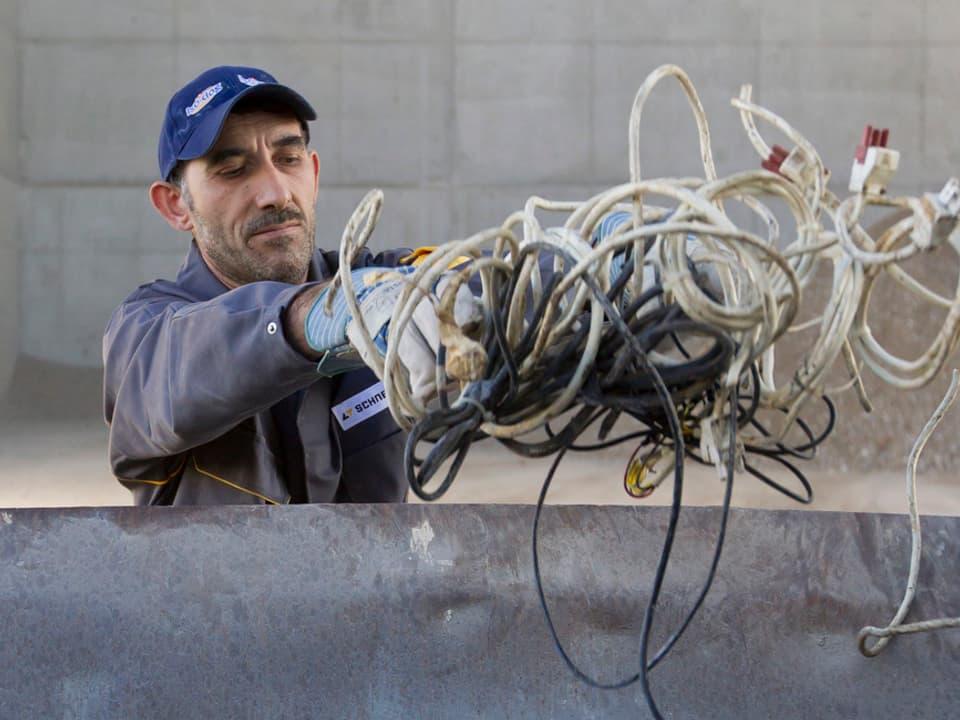 Arbeiter wirft Kabel in Container.