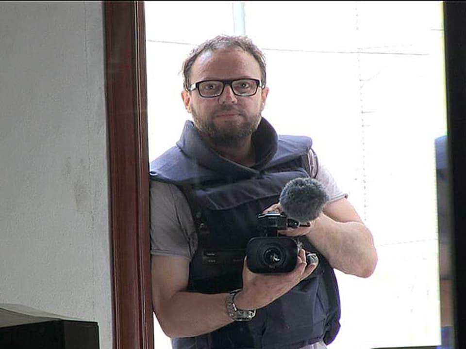 Kurt Pelda mit Filmkamera im Spiegel.