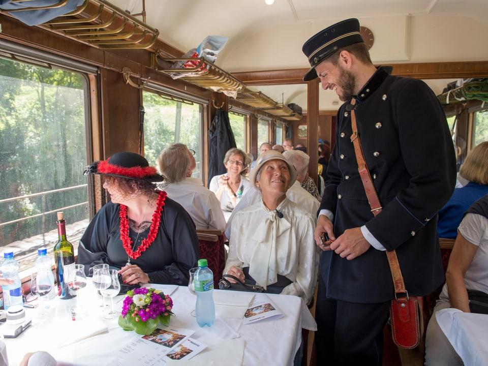 In einem Zug-Speisewagen sitzt eine ältere Dame am Tisch, nebenan ein Kondukteur
