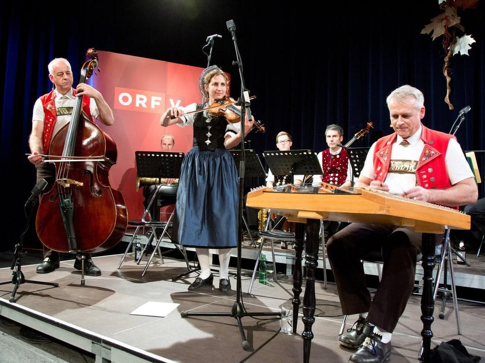 Ein Bassgeiger, eine Violinistin und ein Hackbrettspieler während eines Auftritts.