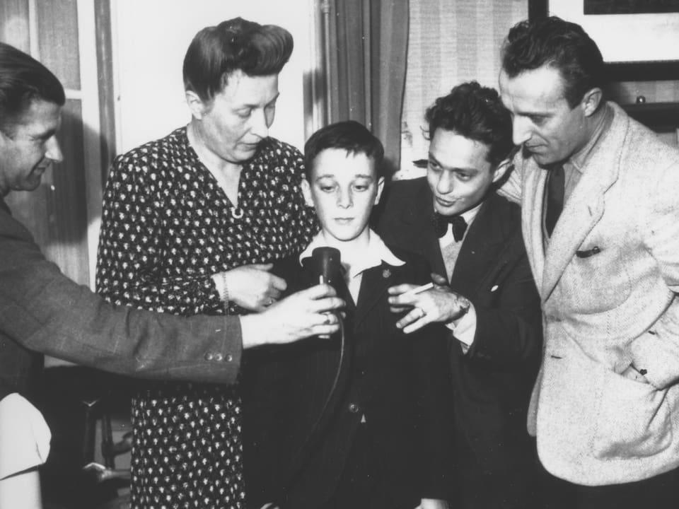 Vier Erwachsene umringen einen Waisenknaben und halten ihm ein Radiomikrofon hin.