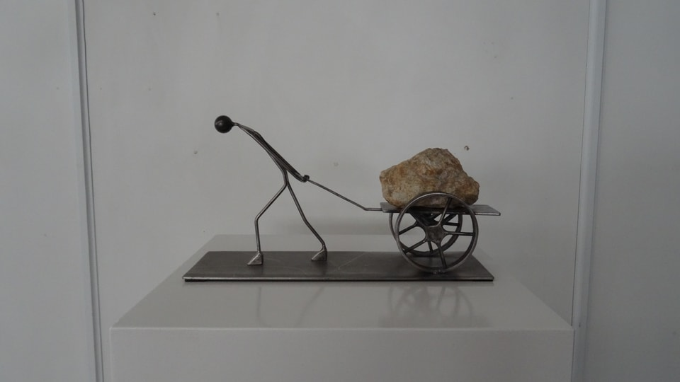 La figura da l'artist Fis Guldimann ch'è da vesair en l'exposiziun «Flucht nach vorn» - um che tira in char cun si in crap