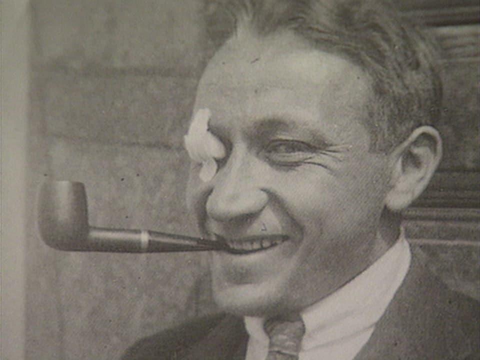 Arthur Caflisch ga giuven cun ina pipa en bucca.
