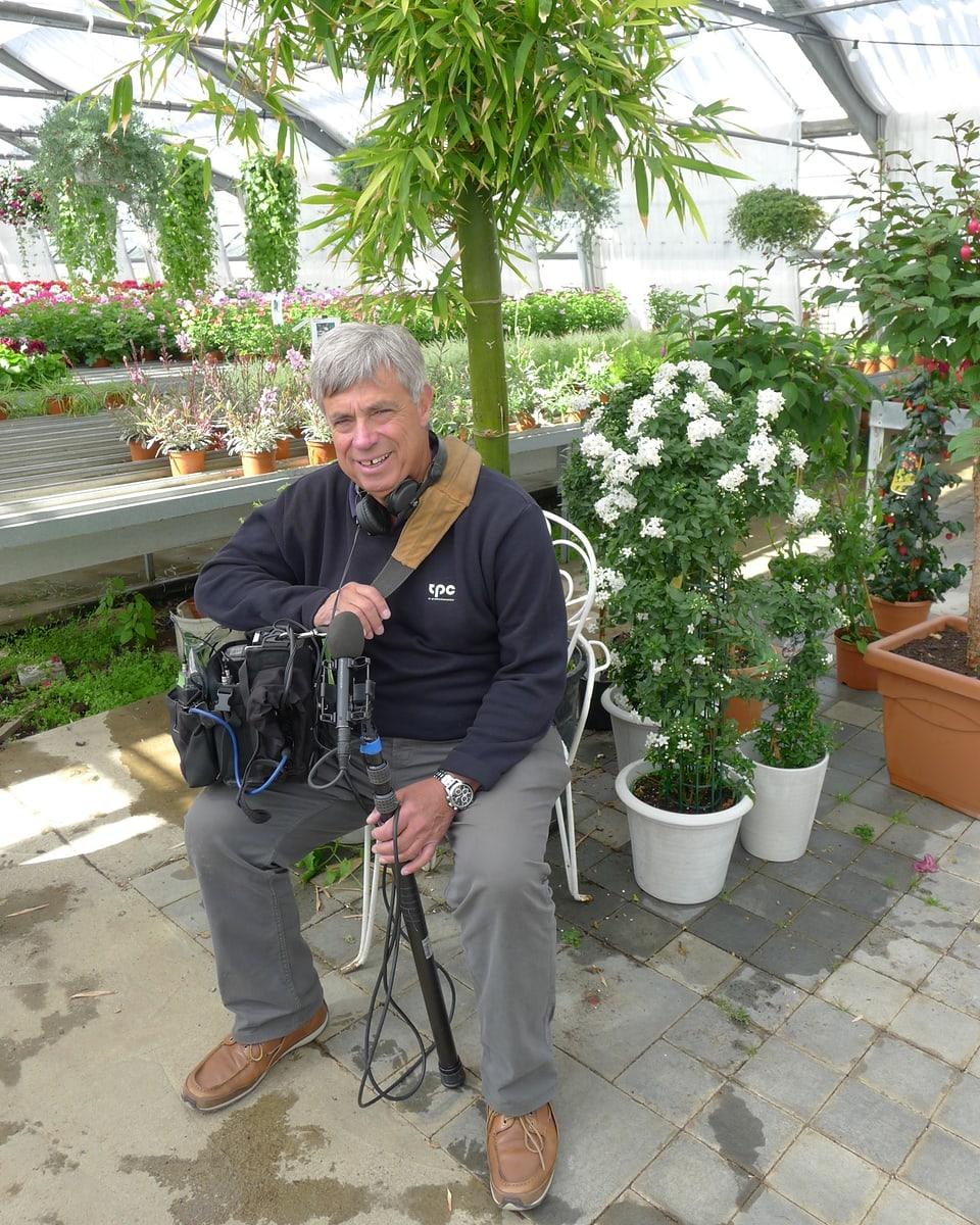 Der Tonoperateur Heinz Kurz gönnt sich eine kurze Verschnaufpause. Er sitzt auf einem weissen Metallstuhl vor einem Bambus.