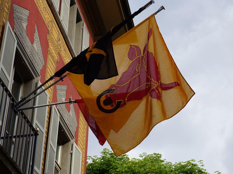 Die Urner Fahne an einer Hausfassade.