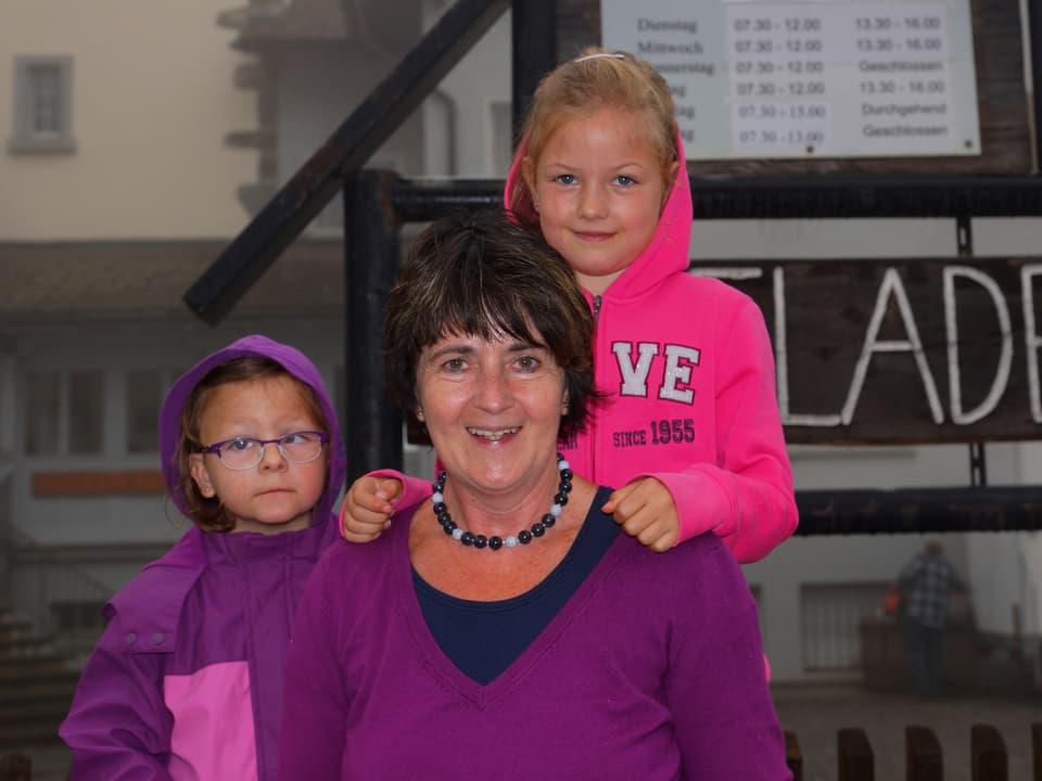Die Grossmutter und ihre Enkelinnen in warmer, lila- und rosafarbigen Kleidern.