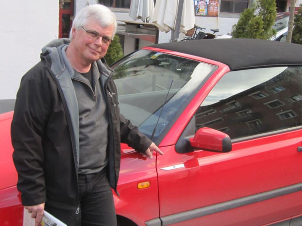 Ein Mann mit grauem Haar und Brille steht vor einem roten Golf.