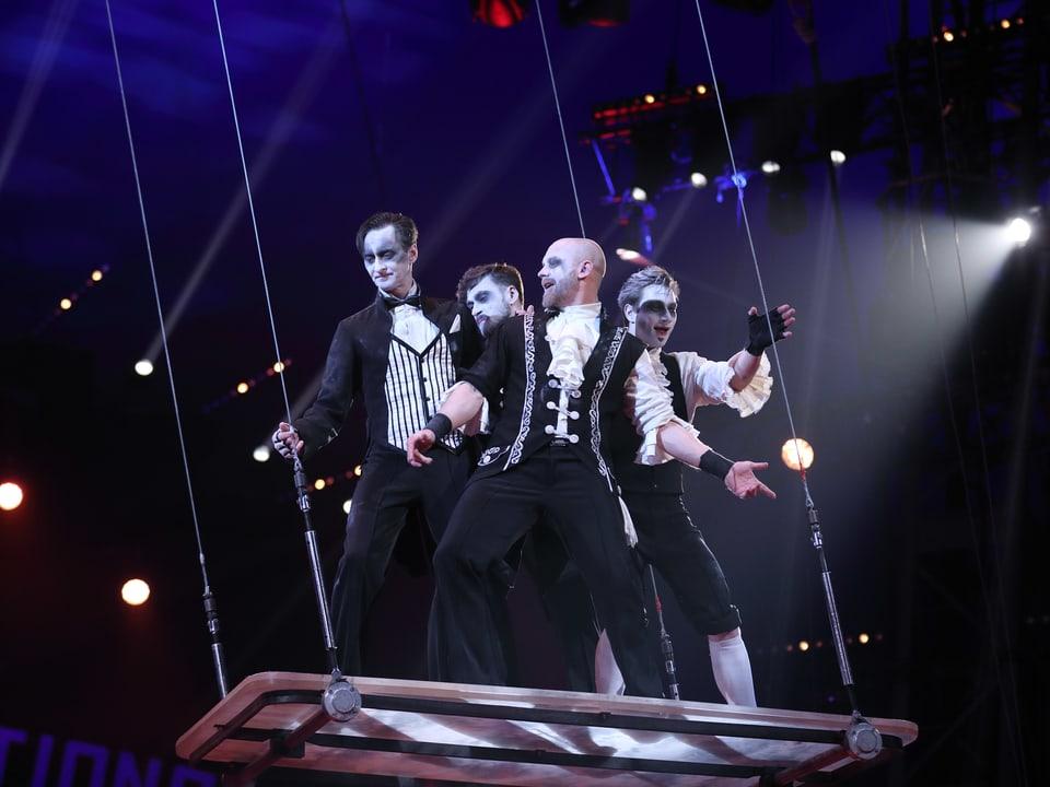 Weiss geschminkte Artisten auf einer Trapez-Plattform.