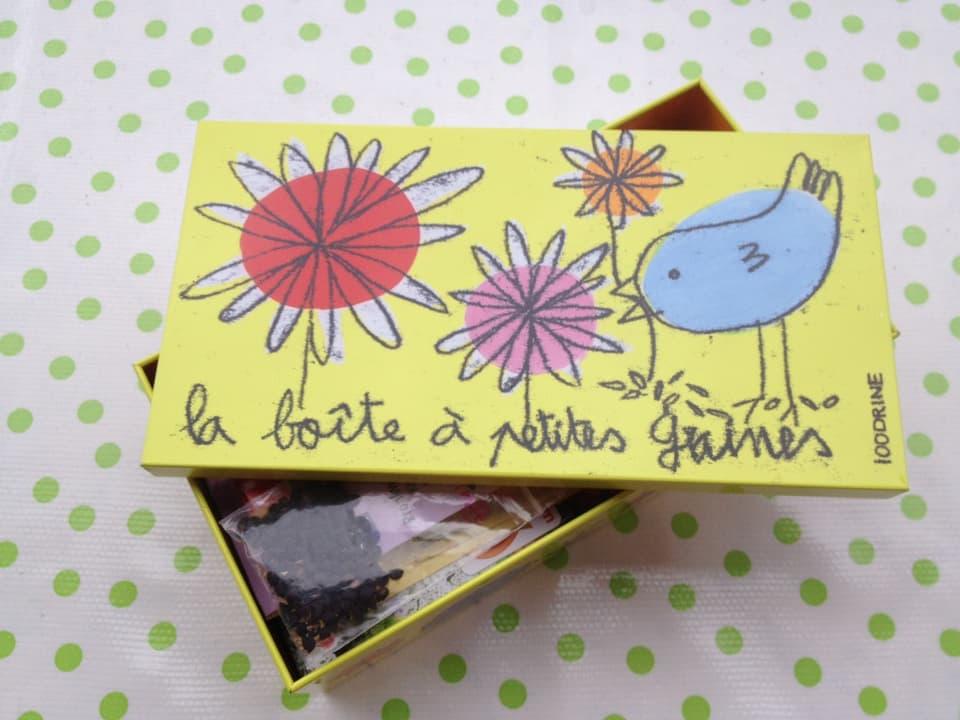 Eine kleine gelbe Schachtel mit aufgezeichneten Blumen und einem hellblauen Vogel, beschrieben mit «la boîte à petites graines».