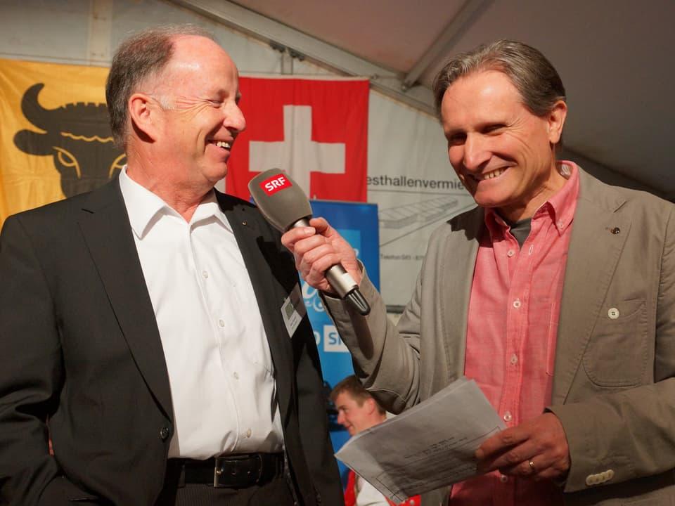 Josef Arnold und Beat Tschümperlin lachend auf der Bühne.