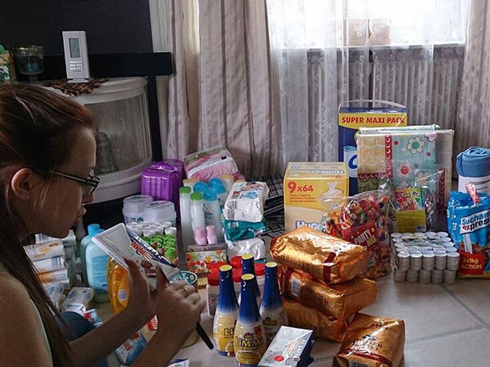 Mädchen mit Hilfsgütern wie Lebensmittel und Waschmittel.