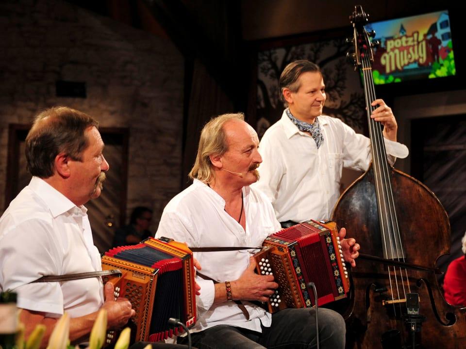 Im Bild drei Musiker, 2 mit Schwyzerörgeli, 1 mit Kontrabass