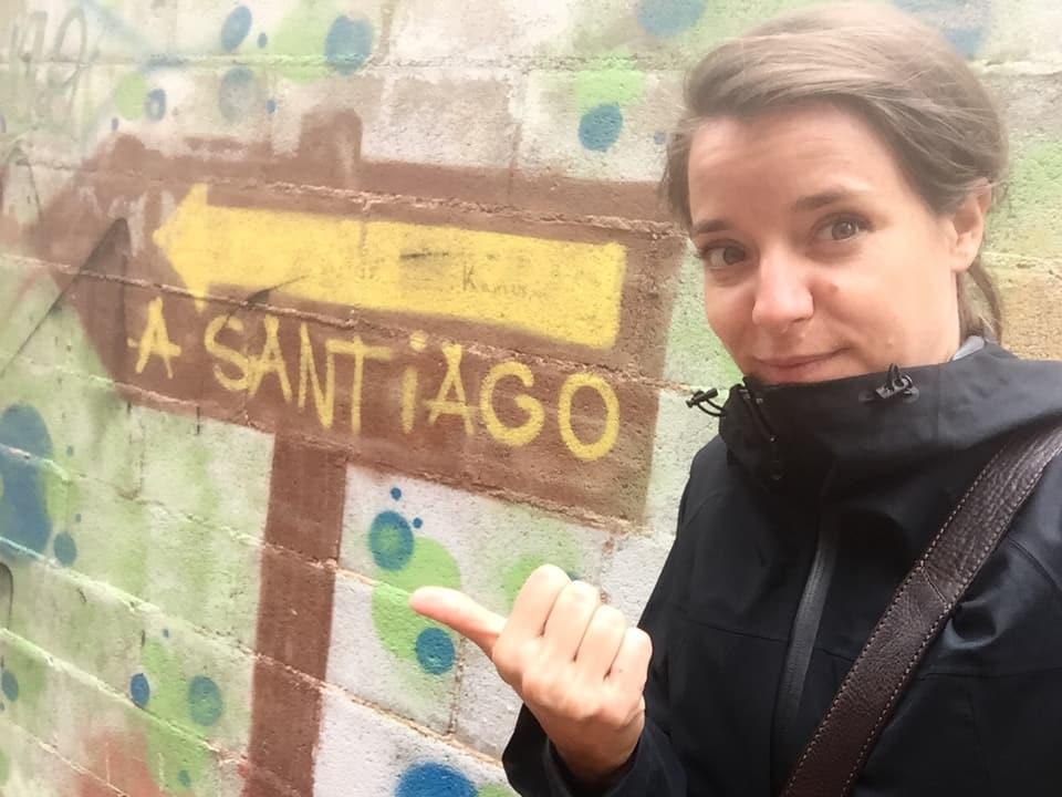 Reporterin Patricia Banzer vor einem Pfeil der nach Santiago zeigt
