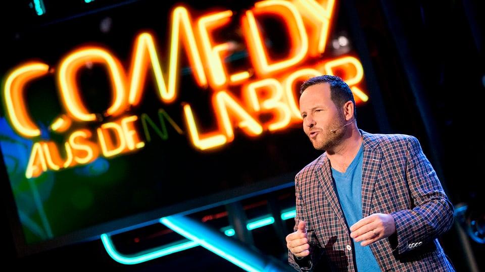 Claudio Zuccolini vor dem Comedy aus dem labor Logo auf der Bühne.