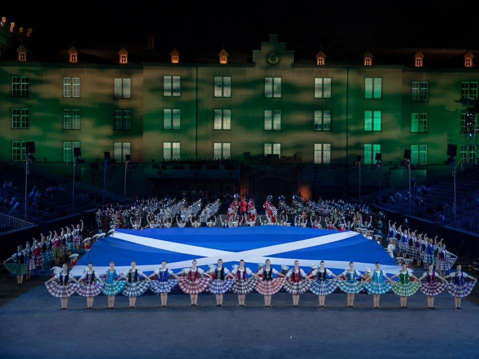Schottische Flagge inmitten von Musikern und Tänzerinnen.
