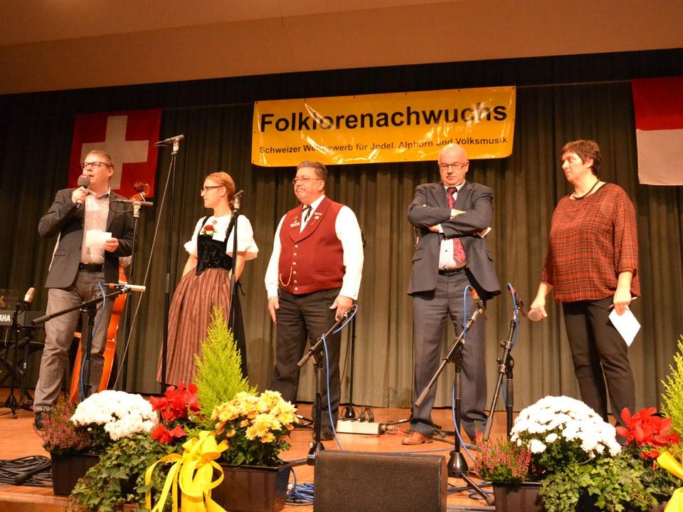 Fünf Personen, die auf einer Bühne stehen.