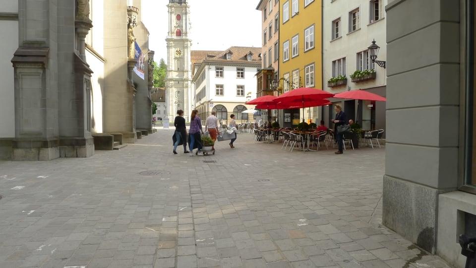 Die vier Personen queren eine Gasse der Sankt Galler Altstadt. Im Hintergrund sieht man einen Kirchturm, im Vordergrund ein Strassencafé mit roten Sonnenschirmen.