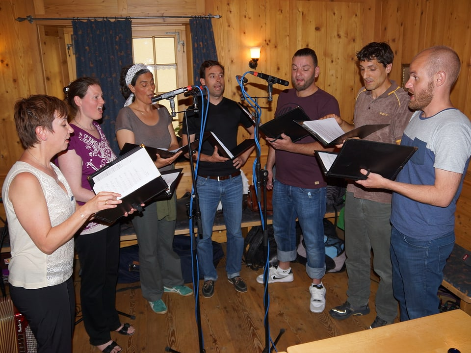 Die Sängerinnen und Sänger stehen mit ihren Notenblättern im Halbkreis vor den Mikrofonen und singen.